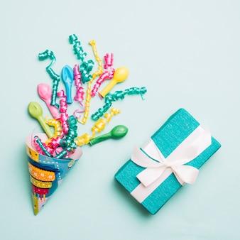 Partyhut mit luftschlangen; ballons und verpacktes geschenk auf blauem hintergrund