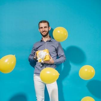 Partyjunge, der mit geschenk und ballonen aufwirft