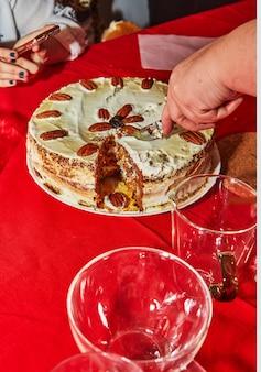 Partykuchen, mit einem messer auf dem tisch in stücke schneiden