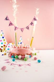 Partykuchen mit farbe besprüht und wunderkerzen. willkommen zurück konzept
