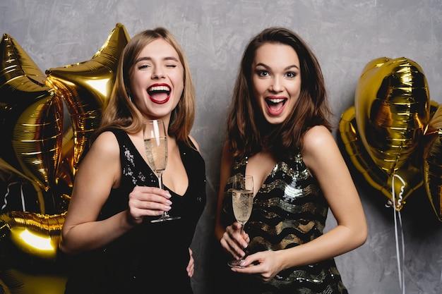 Partyspaß. schöne mädchen, die neues jahr feiern. portrait von wunderschönen lächelnden jungen frauen, die party-feier genießen und gemeinsam spaß haben. hochwertiges bild.