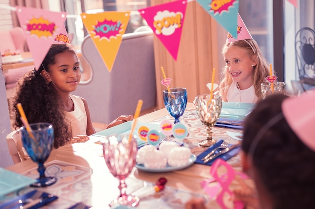 Partytisch. kleine mädchen fühlen sich glücklich und lächeln, während sie während der party am tisch sitzen