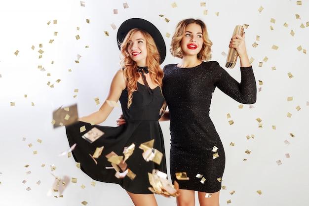 Partyzeit von zwei besten freunden, blonde frauen im eleganten kleid des schwarzen cocktails, das im studio auf weißem hintergrund aufwirft. funkelndes goldenes konfetti. wellenförmige frisur.