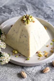 Paskha und kulich mit pistazien. traditioneller russisch-orthodoxer osterquark-dessertquark. ostern essen hintergrund. traditioneller hüttenkäsekuchen