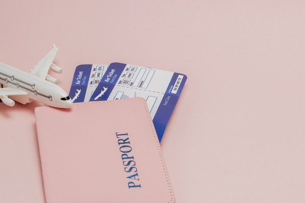 Pass, dollar, flugzeug und flugticket auf einem rosa hintergrund. reisekonzept, kopie, raum