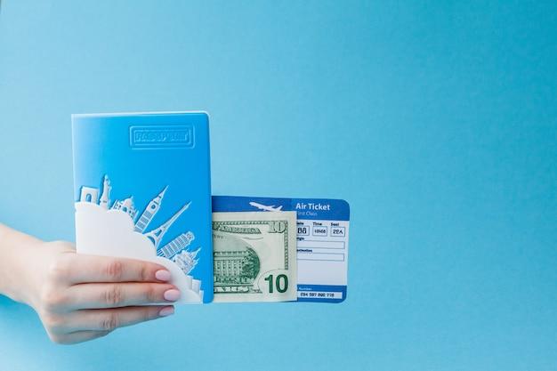Pass, dollar und flugticket in der frauenhand auf einem blauen hintergrund