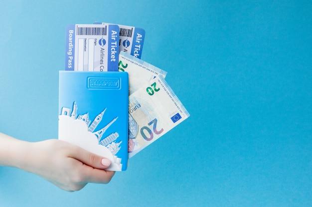 Pass, euro und flugticket in frauenhand auf blauem hintergrund