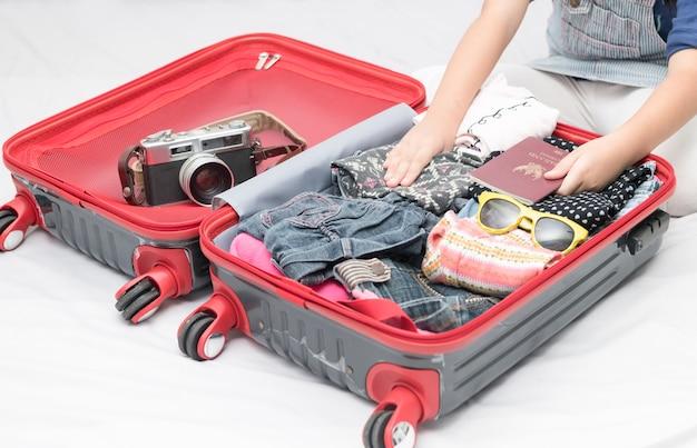 Pass in mädchenhand und reisezubehörkostüme, gepäck, kamera, kleidung im koffer auf dem bett,