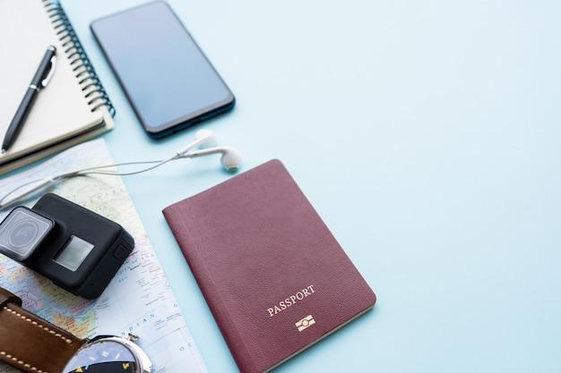 Pass mit einer karte auf blauem pastellhintergrund reiseplanung draufsicht des reisendzubehörs mit kamera, uhr auf weltkarte vorbereitung für reise.