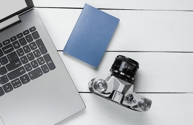 Pass, retro-kamera auf weißem hölzernem hintergrund mit laptop