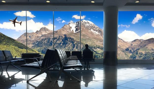 Passagier, der auf den flug für ferien in den bergen wartet