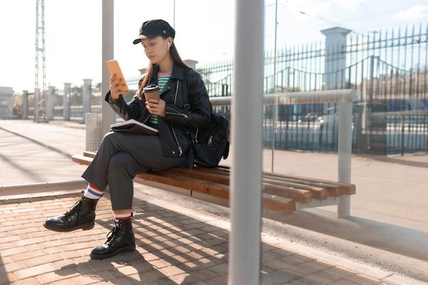 Passagier, der auf einer stationsbank sitzt und handy benutzt