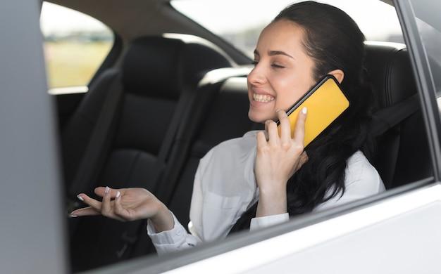 Passagier, der im auto sitzt und am telefon spricht