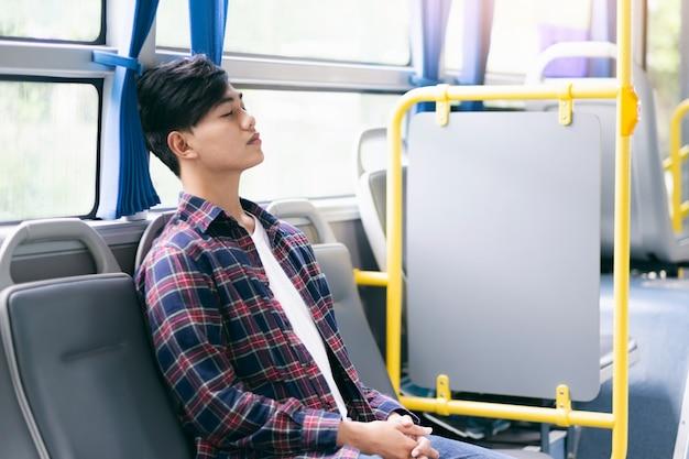 Passagier, der innerhalb eines öffentlichen busses beim reisen sitzt und schläft.