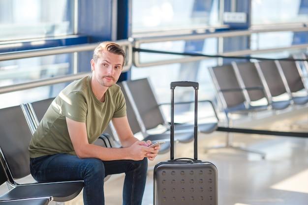 Passagier in einem flughafenaufenthaltsraum, der auf flugflugzeuge wartet