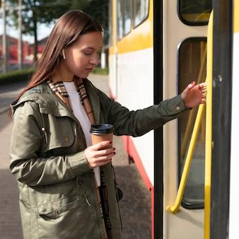Passagier mit seitenansicht, der in die straßenbahn einsteigt