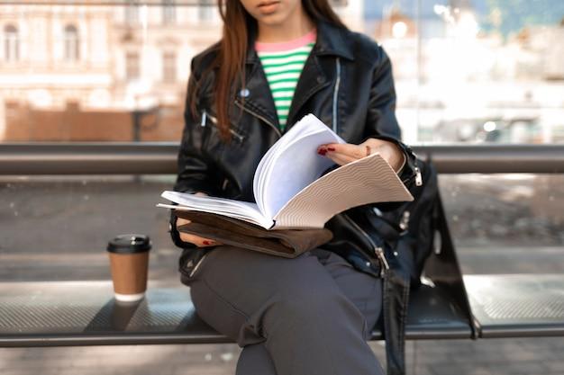 Passagier sitzt auf einer bahnhofsbank und liest
