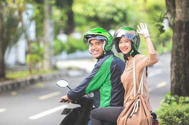 Passagier winkt zum abschied, während er auf einem kommerziellen motorrad sitzt