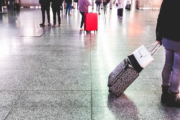 Passagiere am bahnhof warten während der ferien mit ihrem gepäck.