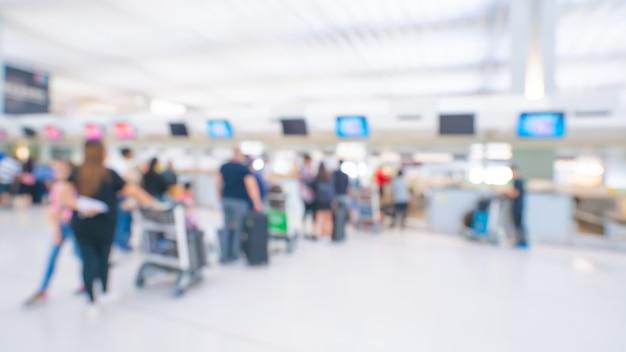 Passagiere am flughafenabfertigungsgebäude verwischten hintergrund