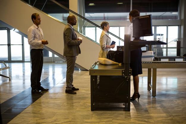 Passagiere, die mit gepäck in der warteschlange an einem check-in-schalter warten