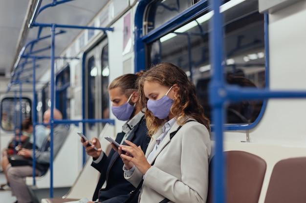 Passagiere, die schutzmasken mit ihrem smartphone tragen, während sie in einem u-bahn-wagen sitzen