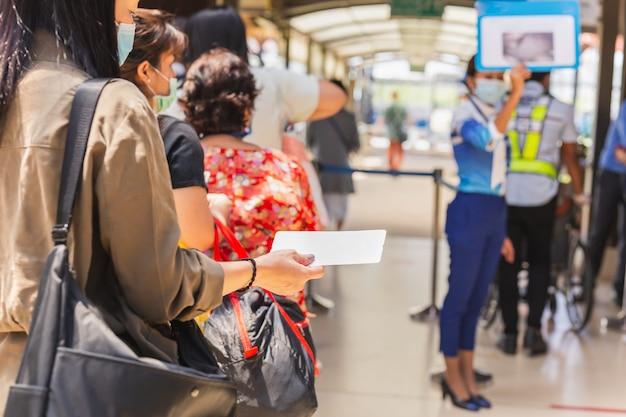 Passagiere in medizinischer maske, die bordkarte halten, die für abflug anstehen.