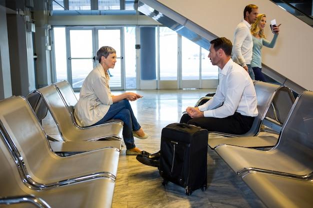 Passagiere mit koffer interagieren im wartebereich