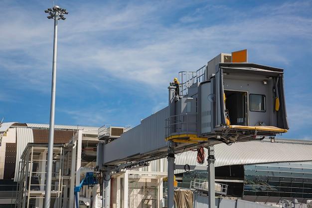 Passagiere sind mit flugzeugen am flughafen mit blauem himmel verbunden