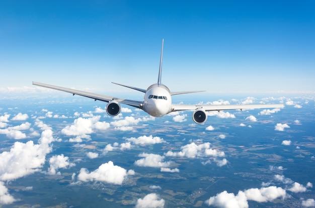 Passagierflugzeug, das auf flughöhe hoch am himmel über cumuluswolken und blauem himmel fliegt. genau direkt davor.
