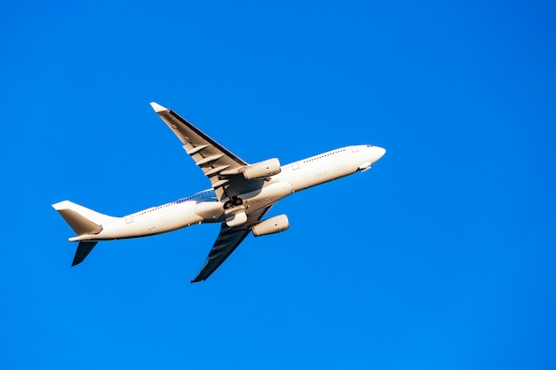 Passagierflugzeug, das im sonnenlicht in die strahlen des blauen himmels fliegt