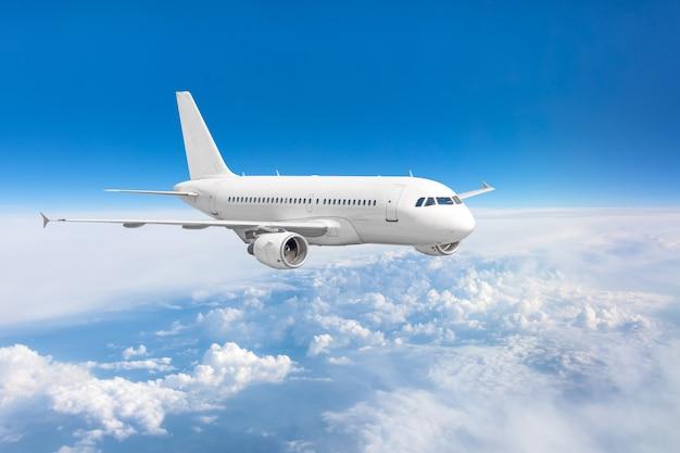 Passagierflugzeug, das über wolken und blauem himmel fliegt.