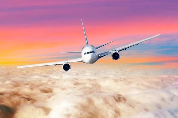 Passagierflugzeug fliegendes flugzeug über dem wolkenhorizont himmel mit hellen sonnenuntergangsfarben. der blick ist genau auf das cockpit der piloten.