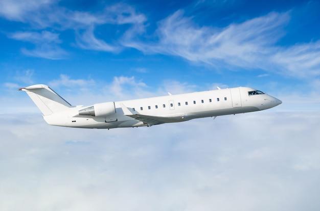 Passagierflugzeug fliegt auf einer flughöhe vor einem hintergrund von wolken und einem blauen himmel