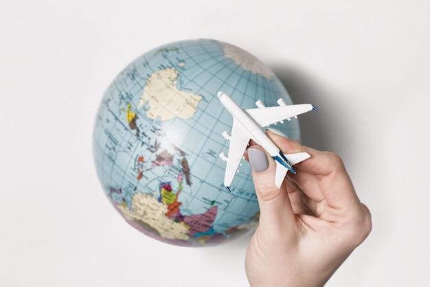 Passagierflugzeug in einer weiblichen hand, erdkugel. flug-konzept