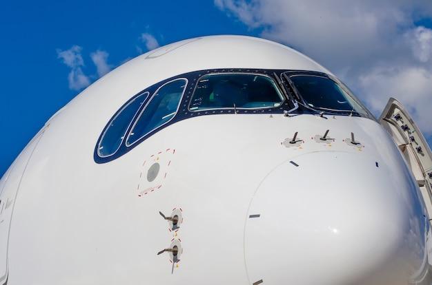 Passagierflugzeugnasencockpit im blauen wolkenhimmel
