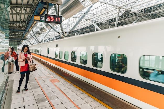 Passagierfrau, die auf taiwan-hochgeschwindigkeitszug wartet.