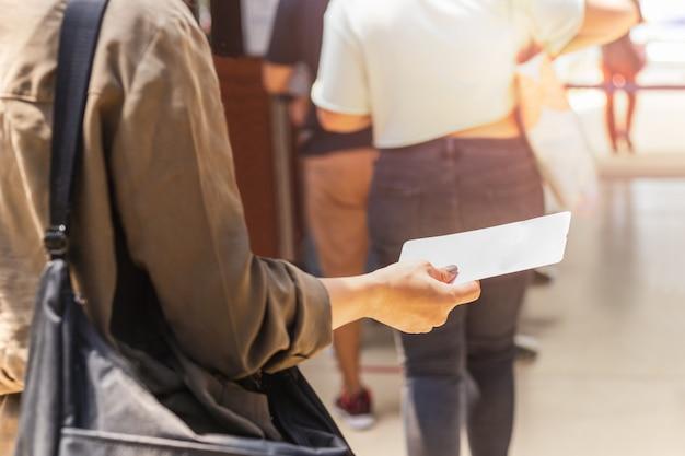 Passagierhand, die bordkarte hält, die für abflug ansteht.