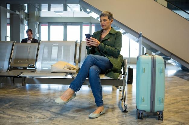 Passagierin, die ihr handy im wartebereich benutzt