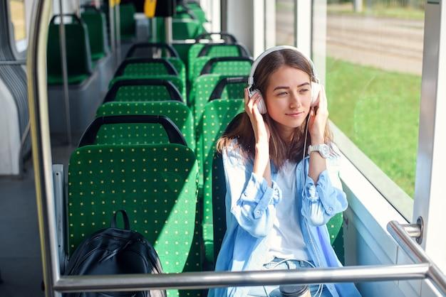 Passagierin hört die musik, während sie in einer modernen stadtbahn fährt, und schaut durch das fenster