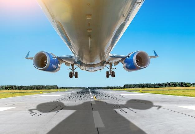 Passagiernahes unteres flugzeug fliegt bei gutem wetter über die start- und landebahn.