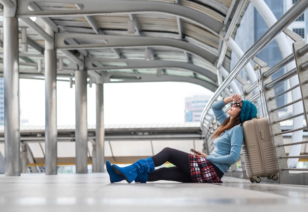 Passagierreisendfrau im flughafenwarteflugzeugverkehr unter verwendung des intelligenten telefons der tablette.