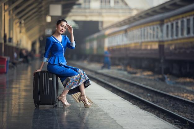 Passagierreisendfrau in der bahnstation, die auf reise wartet.