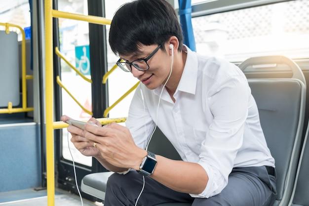 Passagiertransport. leute im bus, musik hören und spiel spielen, während sie nach hause fahren.