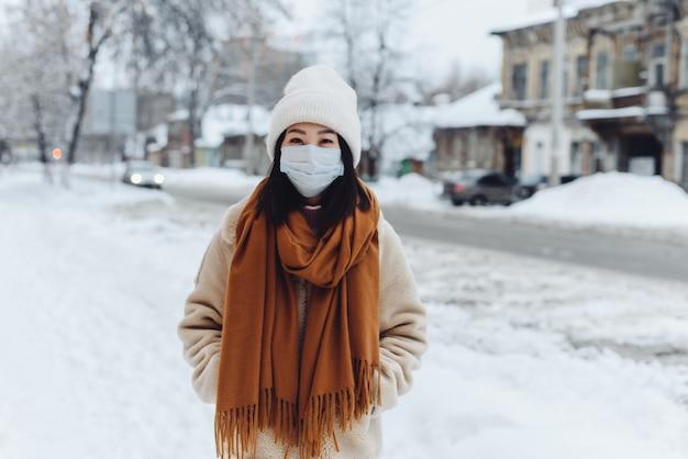 Passant asiatische frau in einer medizinischen schutzmaske im freien. eine frau auf der straße im winter schützt die atemwege vor der coronavirus-epidemie.