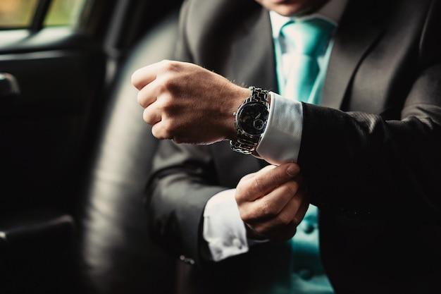 Passen sie an hand des eleganten mannes in einem anzug auf, der im auto sitzt