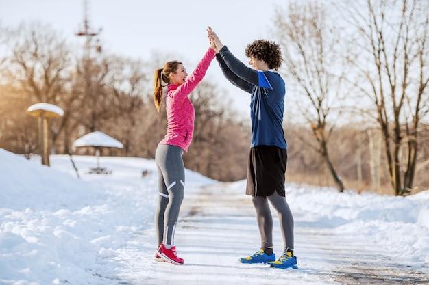 Passen sie fröhliches sportliches kaukasisches paar in sportbekleidung an, die auf landstraße steht und einander hohe fünf gibt. winter. outdoor-fitness-konzept.
