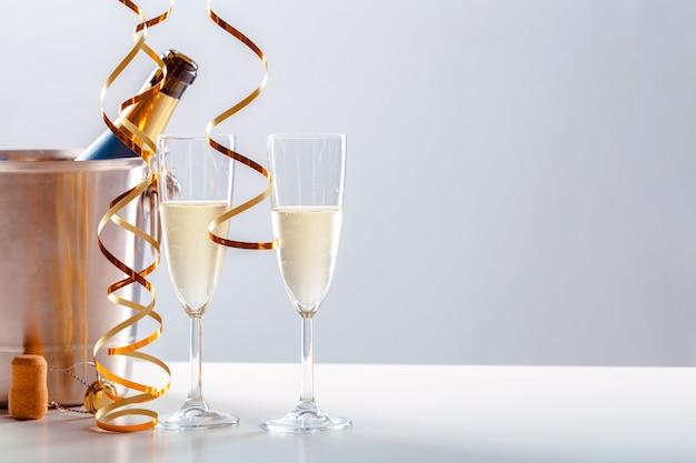 Passen sie glas champagner mit flasche im metallbehälter zusammen. neujahr feierlichkeiten