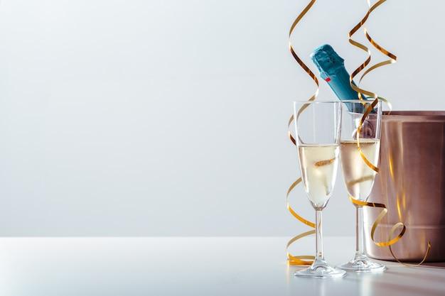 Passen sie glas champagner mit flasche im metallbehälter zusammen