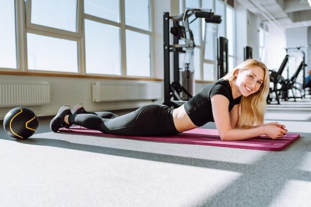 Passen sie junge frau an, die auf übungsmatte im fitnessstudio liegt und entzückend lächelt. gesunde frau machen pause nach dem training.